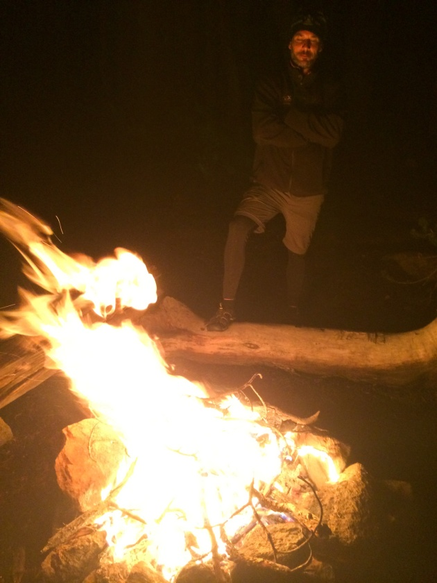 Man standing by campfire