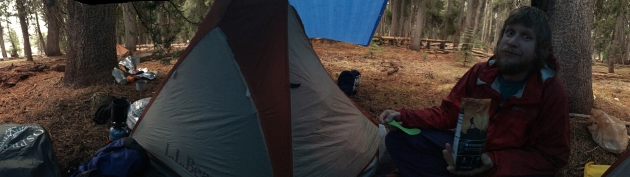Startled man eating next to tent under a tarp
