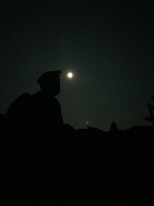 Man in dark below moon