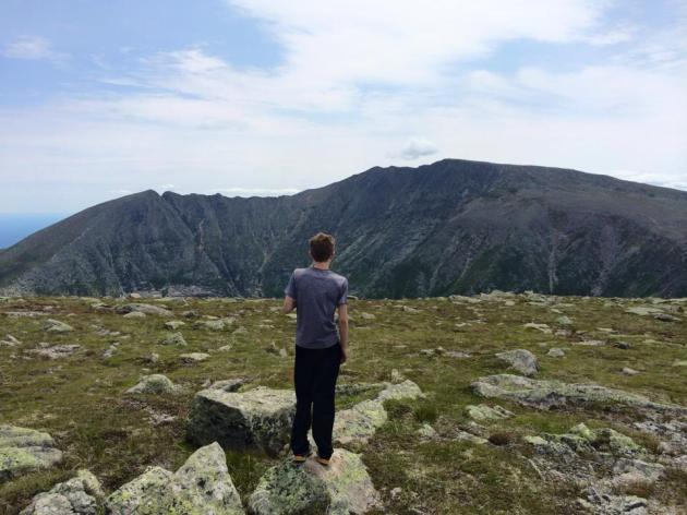 Teenager standing on rock looking at mountains