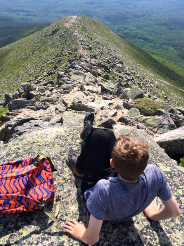 Teenager looking down steep ridge