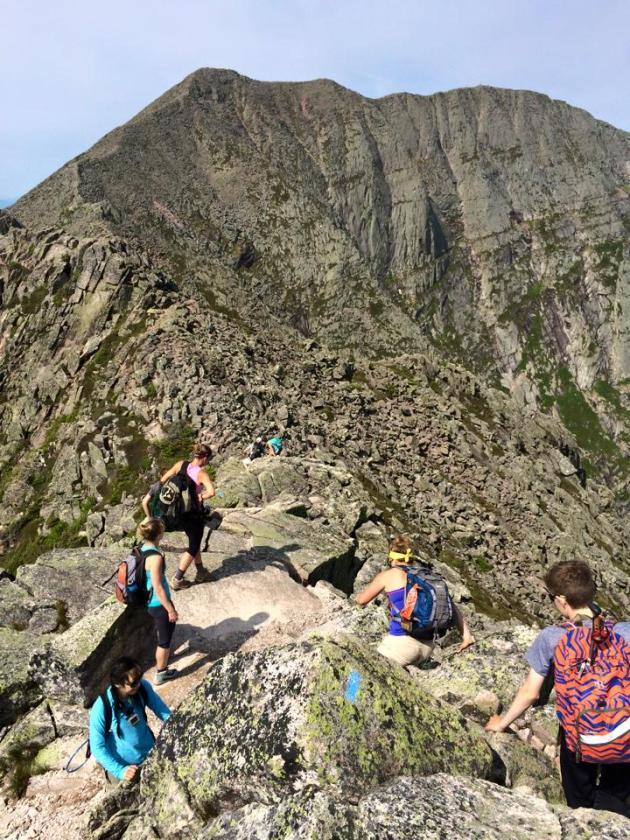 Line of people on steep ridge line
