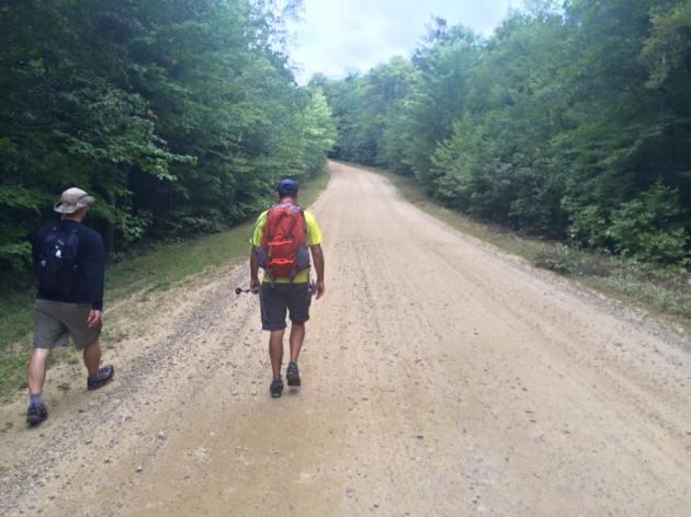 Two men walking on dirt road
