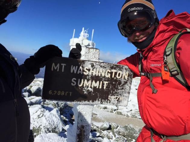 Men at icy summit sign