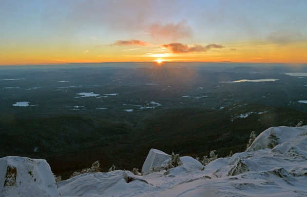 Sun rising above horizon from snowy peak