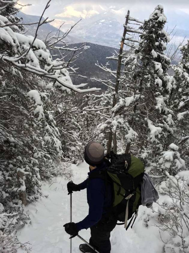 Man on snow covered trail looking at distant mountains