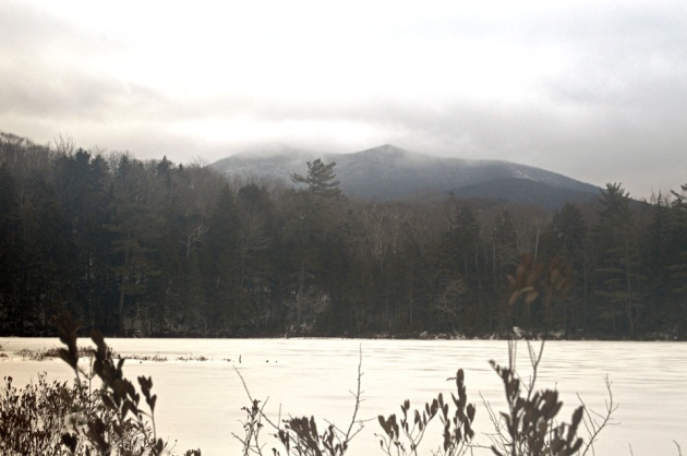 Cloud obscured mountains above frozen pond