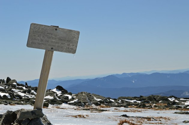 Trail sign with mountains in the background