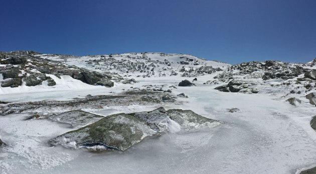Frozen lake surrounded by granite boulders