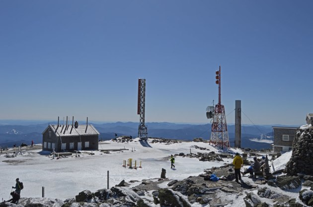 Buildings, radio towers and people at summit of mountain