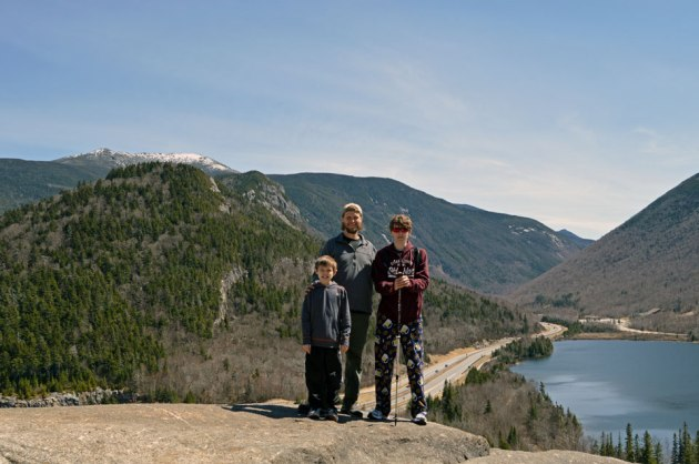 Family standing on cliff with mountains and lake in the background