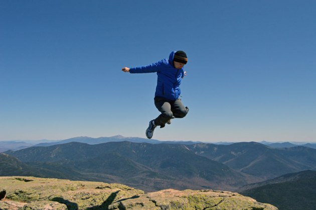 Boy jumping above distant mountains