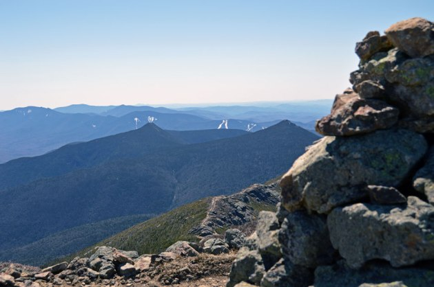 Cairn with mountains and trail in background