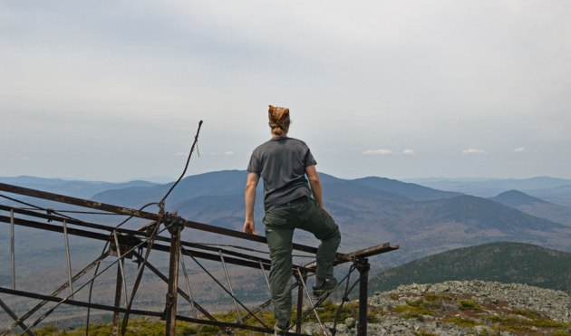 Man standing on metal structure on mountain top and looking at horizon