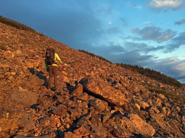 Man hiking up rocks glowing from sunrise