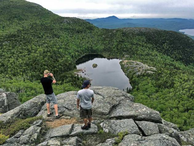 Two men on cliff looking down on pond