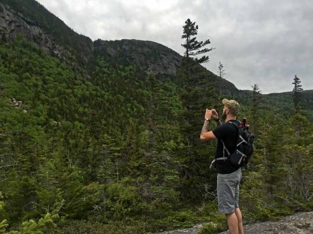 Man looking up at cliffs