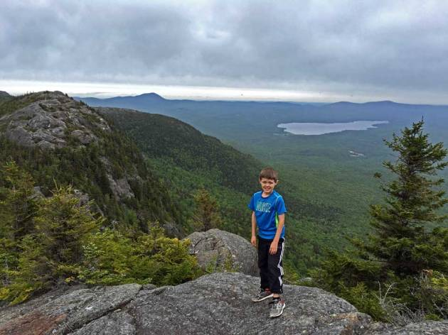 Boy on mountain summit with mountains and lakes in distance