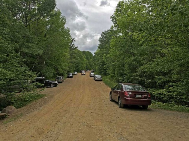 Cars parked on both sides of dirt road