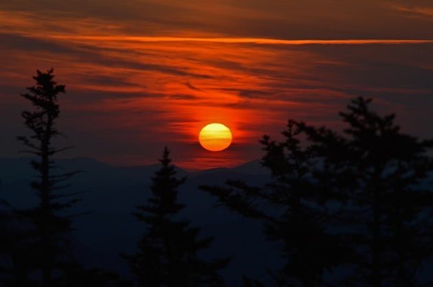 The sun rising over distant mountains
