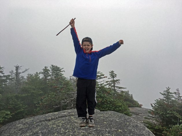 Boy standing on top of mountain