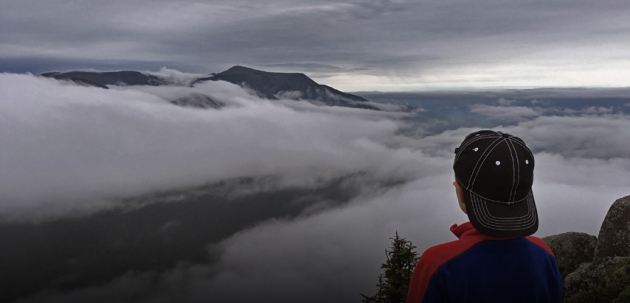 Boy looking over clouds to distant mountain