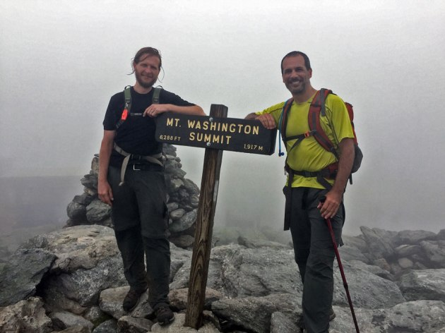 Two men leaning on Mount Washington summit sign