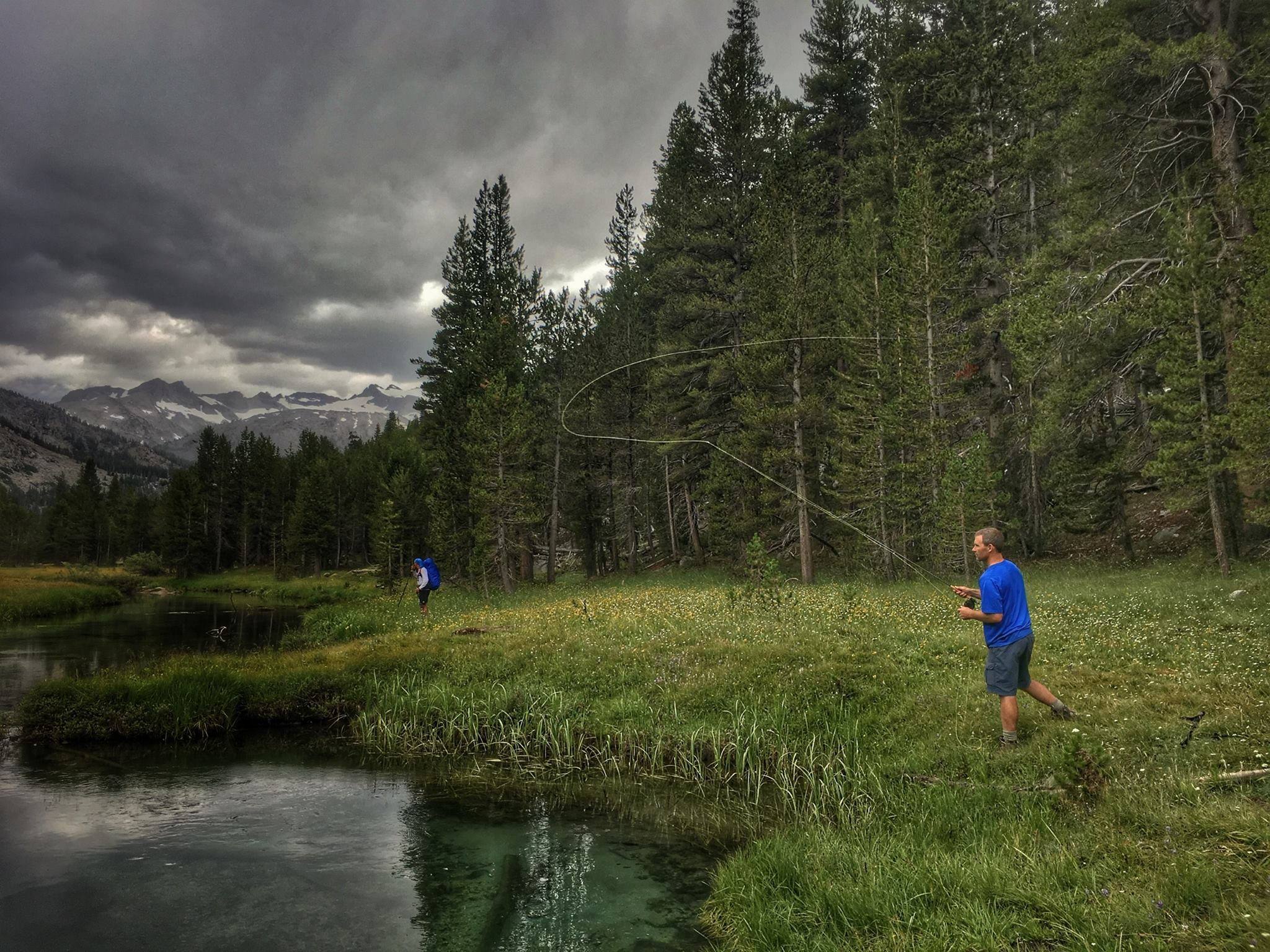 Man fly fishing next to clear brook with snowy mountain in the background