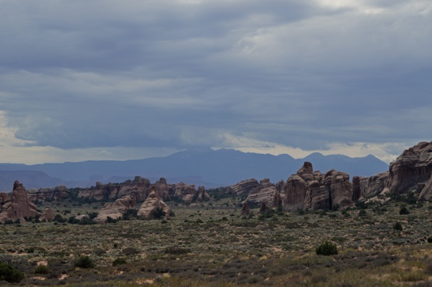 Desert with sandstone spires and mountains in the distance