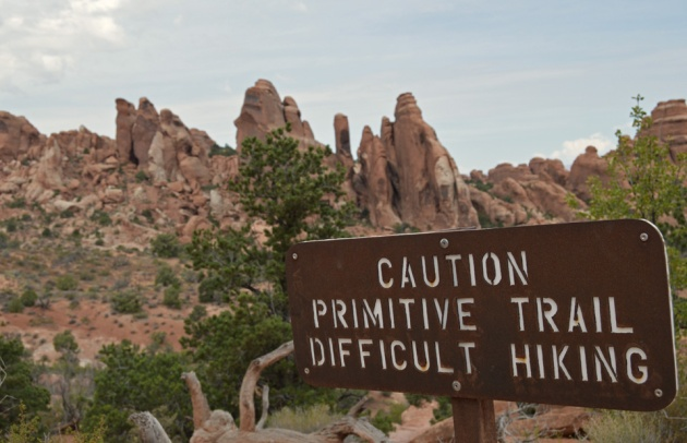 Metal sign reading: caution primitive trail difficult hiking