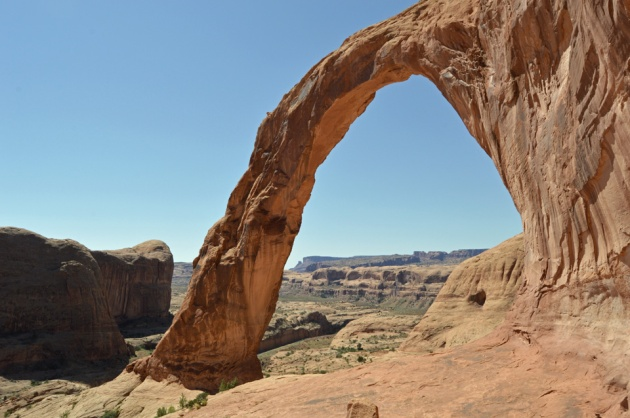 Large stone arch with desert and canyons behind it
