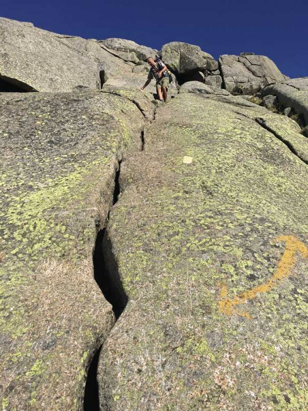 Man climbing down granite rock face with painted trail markers