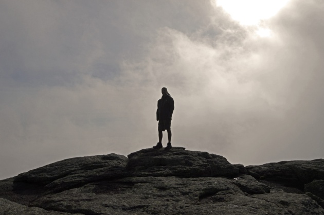 Man on mountain peak with clouds behind him
