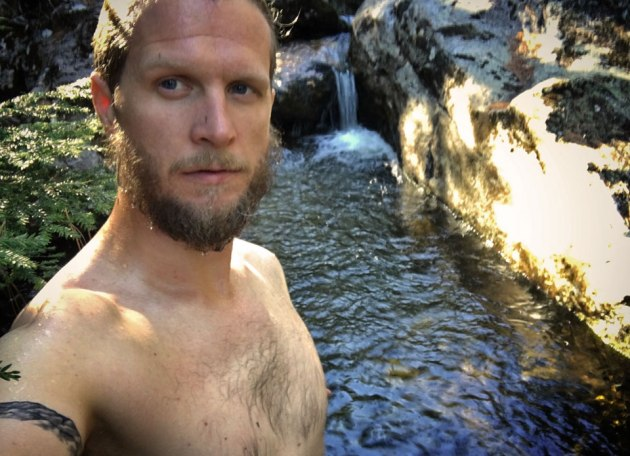 Man in swimming hole with cascades behind him
