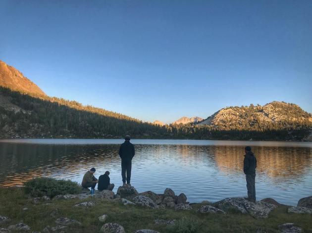 four men lakeside during sunset