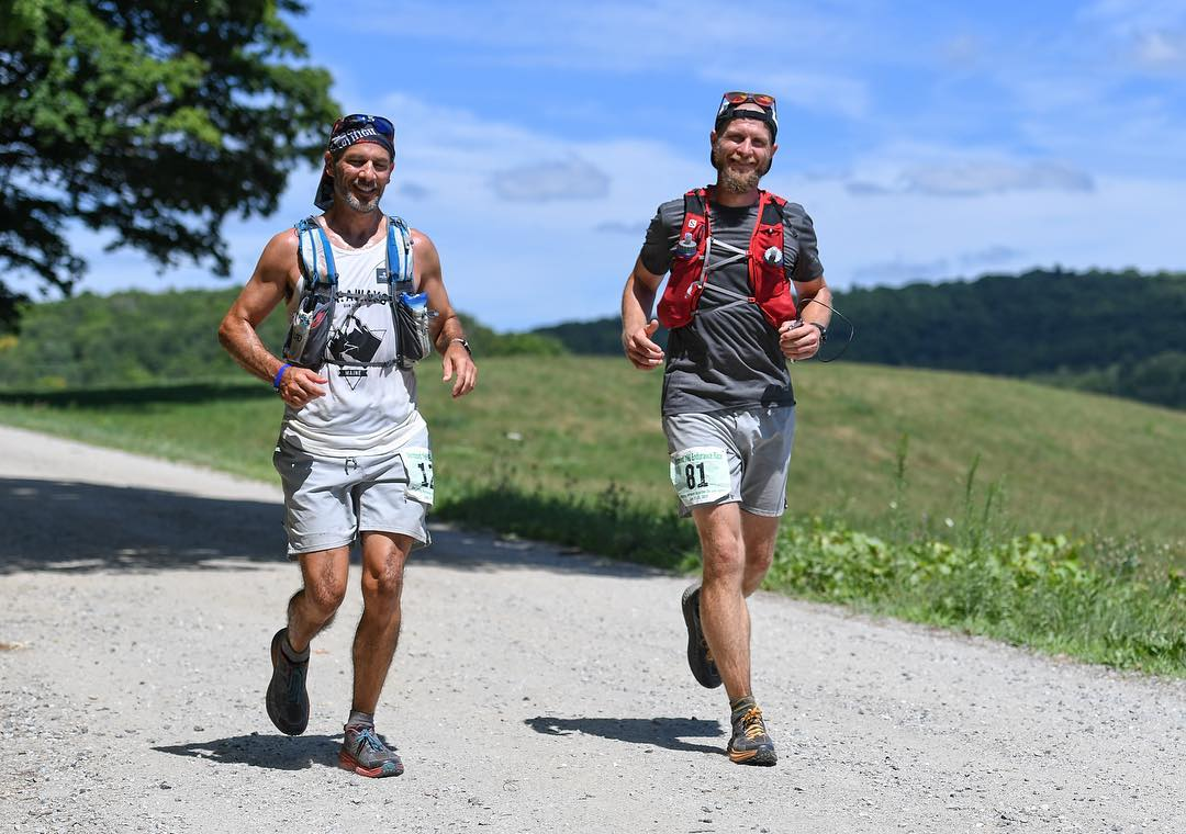two men running on hilly dirt road