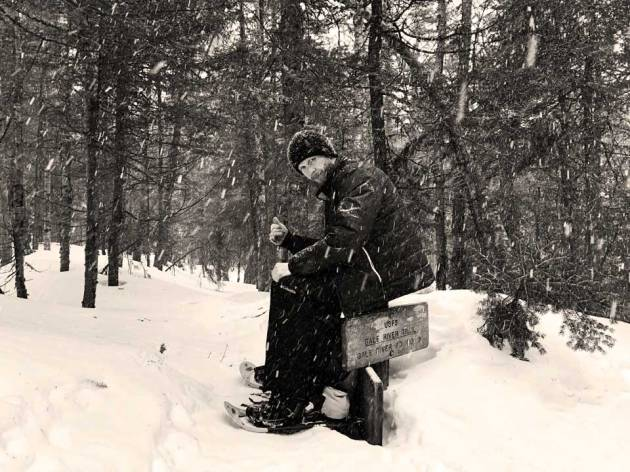 Man siting on trail sign in snow