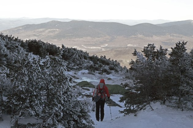 A hiker descending an icy trail with mountains in the background